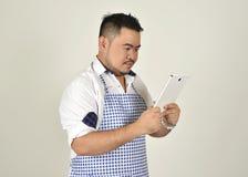 El hombre gordo de Asian del comerciante en el delantal blanco y azul es tecnología del uso leyó noticias de los datos de Interne imagen de archivo libre de regalías
