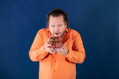 El hombre gordo divertido en camisa anaranjada abre una caja con un regalo foto de archivo libre de regalías