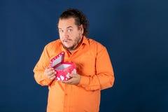El hombre gordo divertido en camisa anaranjada abre una caja con un regalo imagen de archivo