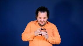 El hombre gordo divertido en camisa anaranjada abre una caja con un regalo metrajes