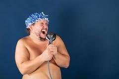 El hombre gordo divertido en casquillo azul canta en la ducha foto de archivo libre de regalías