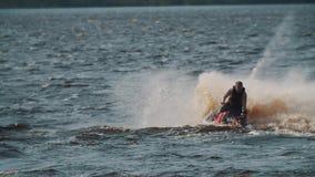 El hombre gordo en esquí del jet del montar a caballo del chaleco de vida en el agua del lago, haciendo da vuelta y salta metrajes
