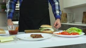 El hombre gordo en un delantal cocina las hamburguesas en casa Todos los ingredientes y productos están en la tabla malsano almacen de video