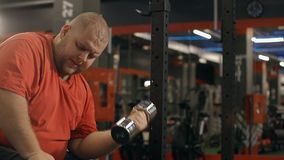 El hombre gordo es entrenamiento pesado en el gimnasio para el cuerpo hermoso y atlético sano almacen de video