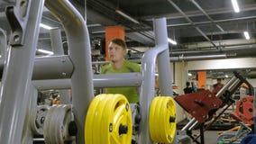El hombre gordo hace posiciones en cuclillas con posiciones en cuclillas con un disco del peso para un barbell Hombre de la aptit metrajes
