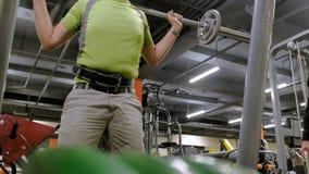 El hombre gordo hace posiciones en cuclillas con posiciones en cuclillas con un disco del peso para un barbell Hombre de la aptit almacen de video