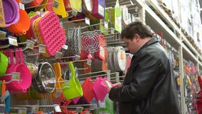 El hombre gordo joven elige los accesorios de la cocina en el supermercado almacen de metraje de vídeo