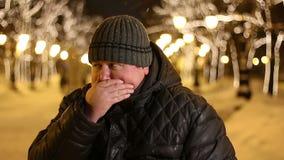 El hombre gordo joven siente nauseabundo y cierra su boca al aire libre en una noche del invierno, almacen de metraje de vídeo