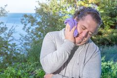El hombre gordo limpia su cara con una situación de la toalla en el océano deporte y una forma de vida sana imagen de archivo