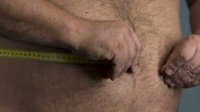 El hombre gordo que intenta medir su vientre en casa se cierra para arriba, dieta de la pérdida de peso almacen de metraje de vídeo