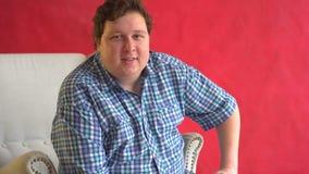 El hombre gordo que se sienta en butaca y está mirando la cámara contra fondo rojo almacen de video