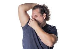 El hombre gordo se sostiene o pellizca la nariz cerrada debido a un olor o un olor stinky fotos de archivo