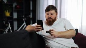 El hombre gordo serio mecanografía varia su tarjeta de crédito en el smartphone que se sienta en el sofá Concepto: pago de un pré metrajes