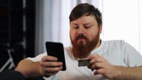 El hombre gordo serio mecanografía varia su tarjeta de crédito en el smartphone que se sienta en el sofá Concepto: pago de un pré almacen de video