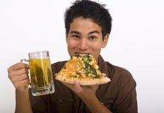 El hombre goza de un vidrio de cerveza y de una pizza Imagen de archivo
