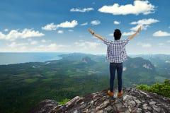 El hombre goza del aire fresco en el pico de montaña Imagenes de archivo