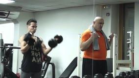 El hombre graso divertido coge las pesas de gimnasia más pequeñas que se colocan al lado de un atleta hermoso