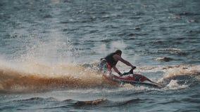 El hombre grueso en esquí del jet del montar a caballo del chaleco de vida en el agua del lago, haciendo da vuelta y salta almacen de metraje de vídeo