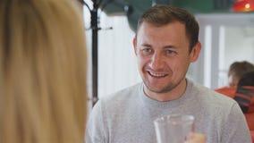 El hombre habla con la esposa durante almuerzo en café en la estación almacen de video