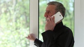 El hombre habla en un smartphone con una mirada seria de la cara almacen de metraje de vídeo