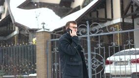 El hombre habla el teléfono cerca del coche costoso metrajes