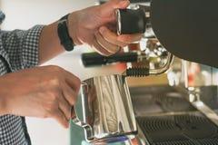 El hombre hace el café con la máquina del café Foto de archivo