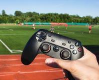 El hombre hace clic en los botones en la palanca de mando del juego en el fondo del estadio y del juego del fútbol, primer imagenes de archivo