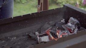 El hombre hace el fuego para una barbacoa El hombre hace una cena La persona infla los carbones La persona infla los carbones una almacen de video