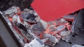 El hombre hace el fuego para una barbacoa El hombre infla el fuego Carbones en un brasero El hombre para balancear una pala sobre almacen de metraje de vídeo