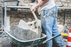 El hombre hace el hormigón en una carretilla en un sitio de la renovación Imagen de archivo libre de regalías