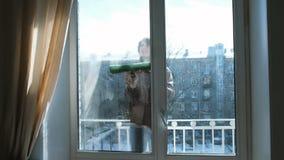 El hombre hace espuma la ventana sucia de sí mismo en casa en el balcón metrajes