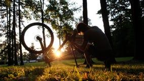 El hombre hace girar la rueda y comprueba la cadena en una bici vuelta hacia arriba en la puesta del sol en el parque fotografía de archivo libre de regalías
