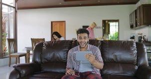 El hombre hace llamada video en línea usando el sitio de Sit On Coach In Living de la tableta, latín Guy Speaking Internet Commun almacen de video