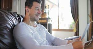 El hombre hace llamada video en línea usando el sitio de Sit On Coach In Living de la tableta, Guy Speaking Internet sonriente almacen de video