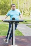 El hombre hace los ejercicios en la máquina del ejercicio de los deportes, cierre para arriba Foto de archivo