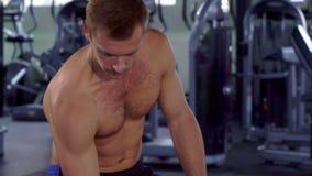El hombre hace los rizos con pesa de gimnasia almacen de video