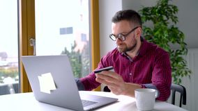 El hombre hace el pago en línea en casa con una tarjeta de crédito y un ordenador portátil almacen de metraje de vídeo
