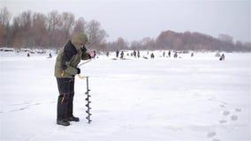 El hombre hace para agujerear el agujero para la pesca del invierno almacen de metraje de vídeo