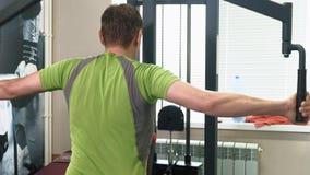 El hombre hace un ejercicio de la mariposa en el simulador en un estudio de la aptitud El concepto de una forma de vida sana Apti almacen de video