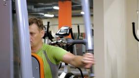 El hombre hace un ejercicio de la mariposa en el simulador en un estudio de la aptitud Forma de vida sana Aptitud y deporte almacen de video