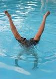 El hombre hace un handstand en una piscina Fotos de archivo libres de regalías