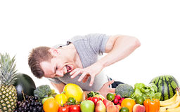 El hombre hambriento ase la fruta y verdura Imagen de archivo