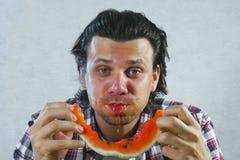 El hombre hambriento come rápidamente una sandía Coma como cerdo imagen de archivo