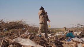 El hombre hambriento sin hogar masculino sucio en forma de vida una descarga que busca la comida de la ropa en el paquete con cam almacen de video