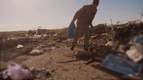 El hombre hambriento sin hogar masculino sucio en una descarga que busca la comida de la ropa en el paquete con caminar va a busc almacen de metraje de vídeo