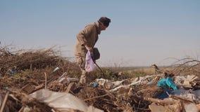 El hombre hambriento sin hogar masculino sucio en una descarga que mira la forma de vida para la comida de la ropa en el paquete  almacen de video