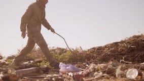 El hombre hambriento sin hogar sucio en una descarga bebe buscar la comida en el paquete con caminar va a buscar la comida lenta almacen de video