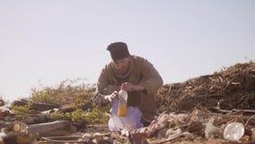 El hombre hambriento sin hogar sucio en una descarga que come la naranja para la comida en forma de vida el paquete con caminar v metrajes
