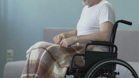 El hombre herido que se sienta en la silla de ruedas, comenzando a empujarla da el esfuerzo recuperarse almacen de video