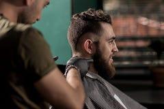 El hombre hermoso brutal con la barba se sienta en una peluquería de caballeros El peluquero afeita los pelos en el cuello fotos de archivo libres de regalías